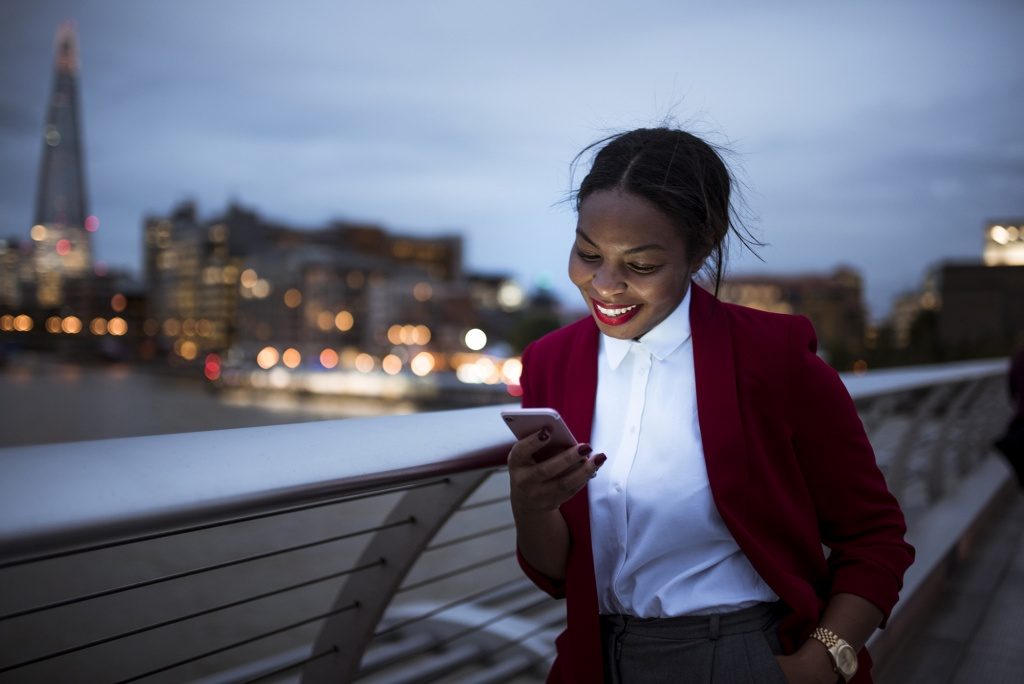 Sales woman looking at her smartphone and smiling